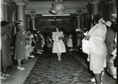 93-historic_79-b_w-photo-of-woman-walking-down-center-of-lobby-with-a-row-of-women-on-each-side-min