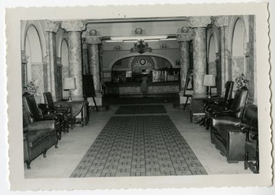 96-historic_82-b_w-photo-of-lobby-with-f_b-counter-with-woman-at-counter-min